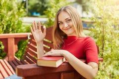 Gelukkig studentenwijfje met licht recht haar en sproeten in rode sweaterzitting die bij bank haar hand bij het grote rode boek g Royalty-vrije Stock Foto