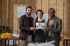 gelukkig team van architecten die miniatuurmodel van de bouw houden royalty-vrije stock fotografie