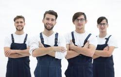 Gelukkig team van verantwoordelijke verhuizers en hun glimlachende leider stock foto