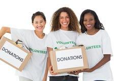 Gelukkig team van vrijwilligers die bij de schenkingendozen van de cameraholding glimlachen stock afbeelding