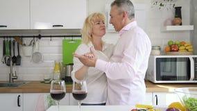 Gelukkig teruggetrokken paar die in comfortabele keuken dansen stock videobeelden