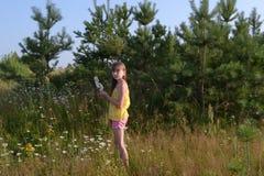 Gelukkig tienermeisje bij de zomerweide, die bloemen verzamelen royalty-vrije stock afbeelding