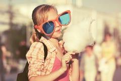 Gelukkig tienermeisje die in zonnebril gesponnen suiker eten die in stadsstraat lopen Royalty-vrije Stock Afbeeldingen