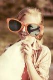 Gelukkig tienermeisje die in zonnebril gesponnen suiker eten openlucht Stock Foto's