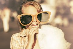Gelukkig tienermeisje die in zonnebril gesponnen suiker eten die in straat lopen stock foto's