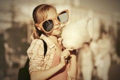 Gelukkig tienermeisje die in zonnebril gesponnen suiker in stadsstraat eten Stock Afbeeldingen