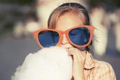 Gelukkig tienermeisje die in zonnebril gesponnen suiker in stadsstraat eten Stock Fotografie