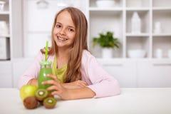 Gelukkig tienermeisje met vers groen vruchtensap in de keuken royalty-vrije stock foto