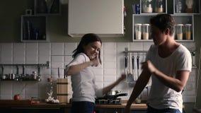 Gelukkig tienerpaar die hebbend pret in de keuken dansen stock video