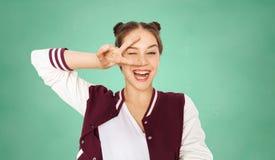 Gelukkig tienerstudentenmeisje die vredesteken tonen stock afbeelding