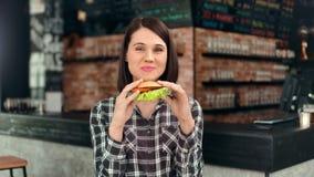 Gelukkig toevallig Europees wijfje die smakelijke sappige hamburger eten bij het middelgrote schot van het snel voedselrestaurant stock videobeelden
