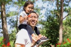 Gelukkig vader en kind die en, gevende dochter op zijn rug bij een openlucht bospark samen lachen spelen stock foto