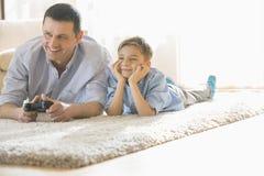 Gelukkig vader en zoons het spelen videospelletje op vloer thuis stock afbeeldingen