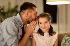Gelukkig vader het fluisteren geheim aan dochter thuis royalty-vrije stock foto
