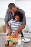 Gelukkig vader snijdend brood met zijn zoon royalty-vrije stock foto