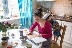 Gelukkig van de familiemamma en zoon thuis keuken samen gelezen boek Stock Fotografie
