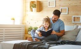 Gelukkig van de familievader en dochter lezingsboek in bed