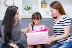 Gelukkig van moeder en dochtervrouw Aziaat en tante met gift met roze lint en dochter kussende moeder stock fotografie