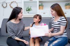 Gelukkig van moeder en dochtervrouw Aziaat en tante met gift met roze lint en dochter kussende moeder stock afbeelding