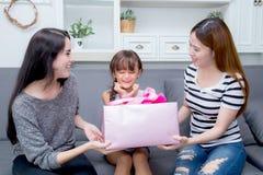 Gelukkig van moeder en dochtervrouw Aziaat en tante met gift met roze lint en dochter kussende moeder stock afbeeldingen