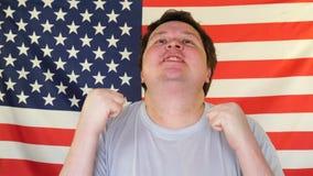 Gelukkig vet mannelijk tonend winnaargebaar, mens in stralen van glorie op de Achtergrond van een Vlag van de V.S. stock footage