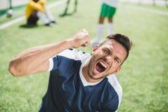 Gelukkig voetballer het vieren doel tijdens voetbalgelijke Royalty-vrije Stock Fotografie