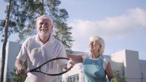 Gelukkig volwassen paar speeltennis op een zonnige dag Een oude man en een rijpe vrouw genieten van het spel Recreatie en Vrije t stock footage