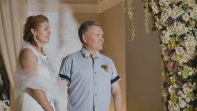 Gelukkig volwassen paar worden die die onder bloemboog wordt gehuwd stock videobeelden