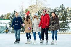 Gelukkig vriendenijs die op piste in openlucht schaatsen Royalty-vrije Stock Afbeeldingen