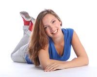 Gelukkig vrij tienerschoolmeisje dat op vloer ligt Stock Foto