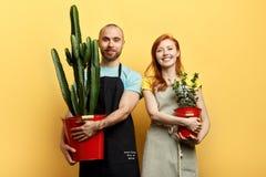 Gelukkig vrolijk jong paar met bloemen die aan de camera stellen stock afbeelding