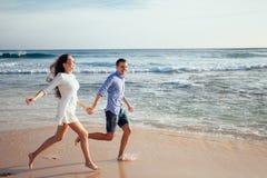 Gelukkig vrolijk paar die pret hebben die aan de oceaan lopen samen en plonsen van water op een tropisch strand doen bij zonsonde royalty-vrije stock fotografie