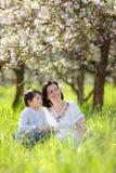 Gelukkig vrouw en kind in de tuin van de de lenteappel Royalty-vrije Stock Foto's