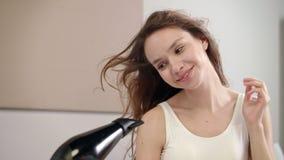 Gelukkig vrouwen drogend haar in badkamers Portret van jong vrouwen droog haar bij ochtend stock video