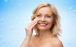 Gelukkig vrouwen schoonmakend gezicht met katoenen stootkussen Royalty-vrije Stock Fotografie