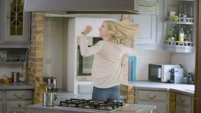 Gelukkig vrouwenhoppen en het dansen rond in de keuken - langzame motie stock footage