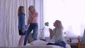 Gelukkig weekend thuis, zusters die en voor hun mamma dansen zingen die zich op bed bevinden stock videobeelden