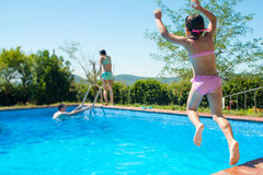 Gelukkig weinig actief meisje die in openlucht zwembadduri springen Stock Afbeelding