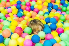 Gelukkig weinig jong geitjejongen die bij de kleurrijke plastic hoge mening van de ballenspeelplaats spelen Grappig kind die pret stock afbeeldingen