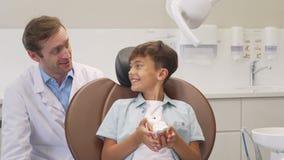 Gelukkig weinig jongen die duimen na succesvolle tandcontrole met tandarts toont stock footage