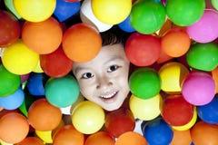 Gelukkig weinig jongen die met kleurrijke ballen speelt Stock Foto's