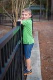 Gelukkig weinig jongen die omheining beklimmen bij park Royalty-vrije Stock Afbeelding