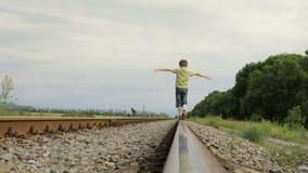 Gelukkig weinig jongen die op de spoorweg in de dagtijd lopen stock footage