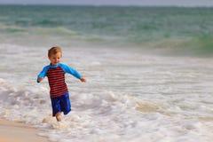 Gelukkig weinig jongen die op de zomerstrand lopen Stock Afbeelding