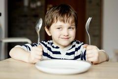 Gelukkig weinig jongen die op diner wachten Royalty-vrije Stock Afbeelding