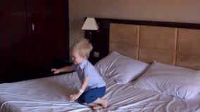 Gelukkig weinig jongen die op het grote bed, langzame mo springen stock videobeelden