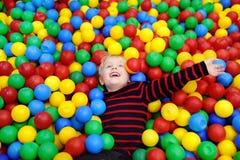 Gelukkig weinig jongen die pret in balkuil hebben met kleurrijke ballen stock foto