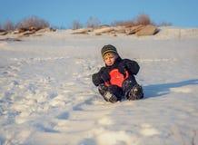 Gelukkig weinig jongen die pret in de wintersneeuw hebben royalty-vrije stock foto's