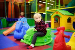 Gelukkig weinig jongen die pret met plastic speelgoed-schommeling/hoppenmotor in spelcentrum hebben stock afbeelding
