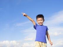 Gelukkig weinig jongen die richting met blauwe hemel richten stock afbeeldingen